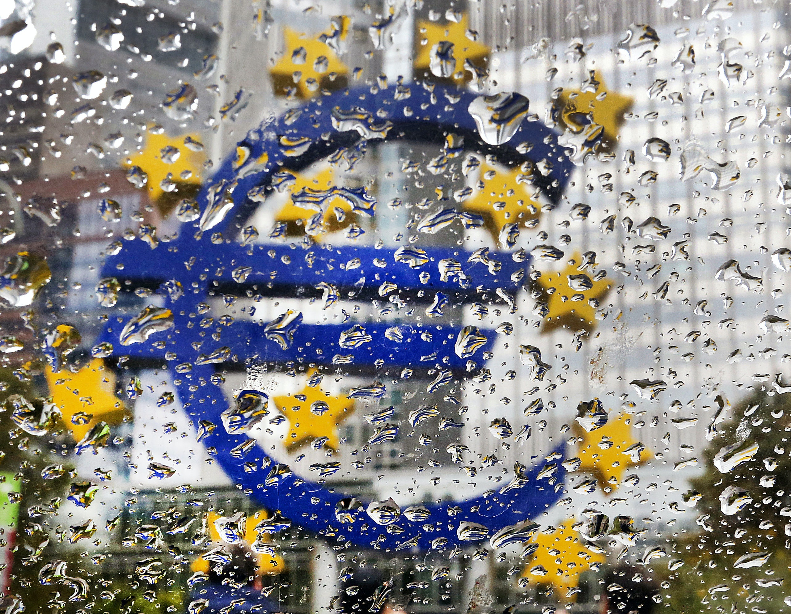 The Euro sculpture in front of the old European Central Bank is photographed behind rain drops on a window in Frankfurt, Germany, Tuesday, Oct. 18, 2016. The governing council of the ECB will meet on Thursday. (AP Photo/Michael Probst)
