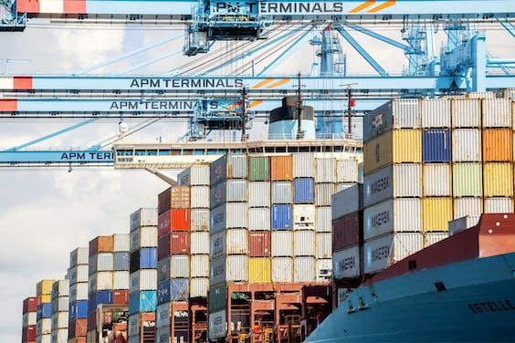 Kranen van APMT in de Rotterdamse haven bij het lossen van een schip van zusterbedrijf Maersk.