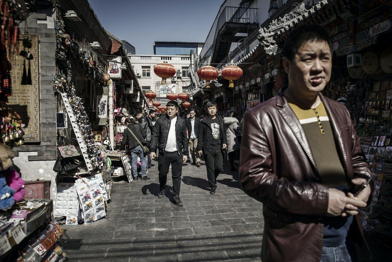 Voetgangers lopen door Wangfujing, een winkelstraat in Beijing.